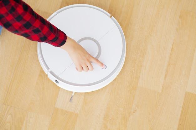Крупным планом женщины включает умный робот-пылесос.