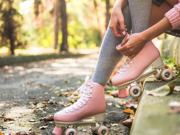 Конец-вверх женщины связывая шнурок на коньках ролика в носках