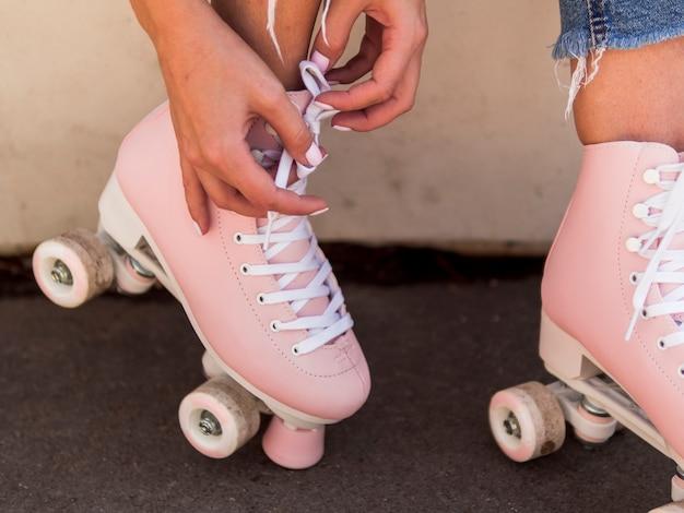 Конец-вверх женщины связывая шнурок на коньках ролика