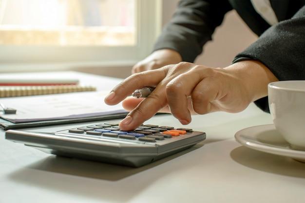 電卓を使用して財務会計、作業、アイデアの保存を行う女性のクローズアップ。