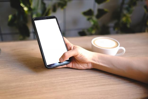 空白の携帯電話注文製品を使用してカフェ内でオンラインショッピングをする女性のクローズアップ。