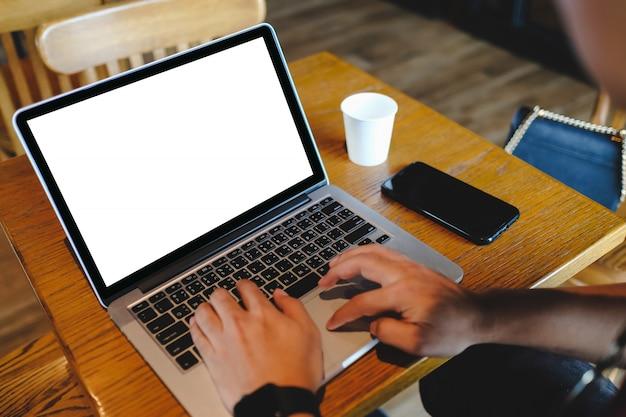 カフェ内でオンラインショッピングするために携帯用ノートパソコン注文商品を使用している女性のクローズアップ。