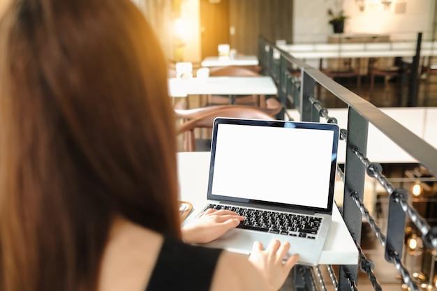 携帯電話とラップトップを使用して女性のクローズアップ、カフェ内でマッサージを送信します。
