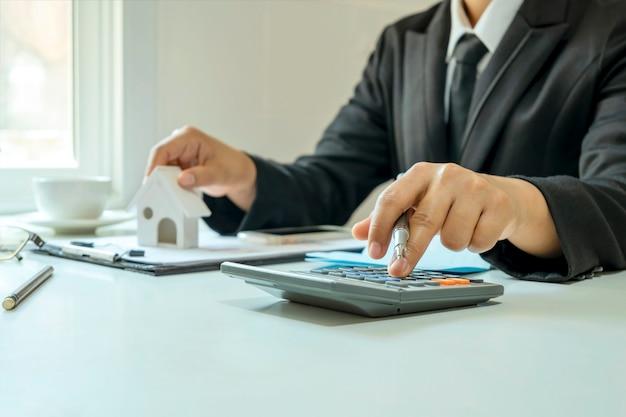 Крупный план женщины, использующей концептуальный калькулятор для расчета экономии денег ипотека, жилая недвижимость