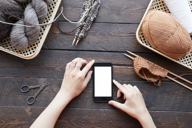 彼女がオンラインで編み物のレッスンを見ている羊毛のボールとテーブルに座っている彼女の携帯電話を使用して女性のクローズアップ