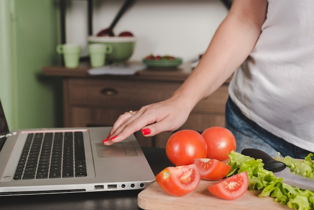 Крупным планом женщина, используя ноутбук с помидорами и салатом на кухне счетчик