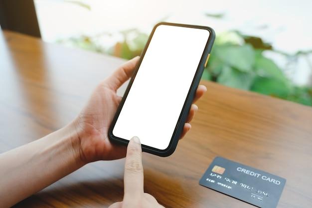 コーヒーショップでマッサージを送信するモバイル空白のスマートフォンとクレジットカードを使用して女性のクローズアップ