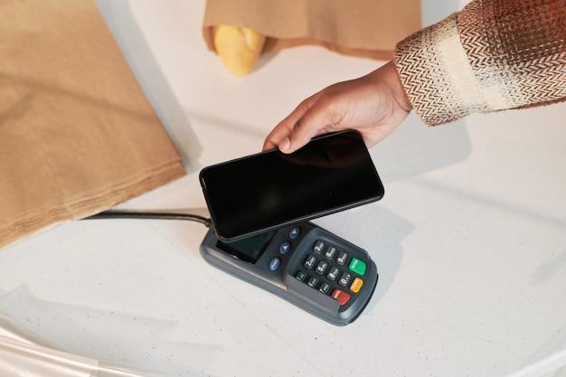 휴대 전화를 사용하고 상점에서 터미널로 온라인으로 지불하는 여성의 클로즈업