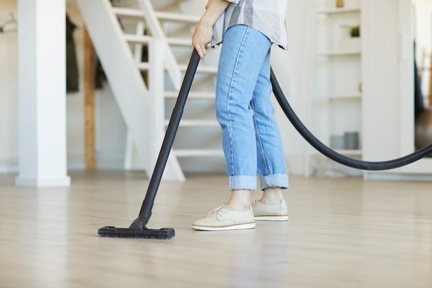 彼女の家の床からほこりを掃除機で掃除する女性のクローズアップ