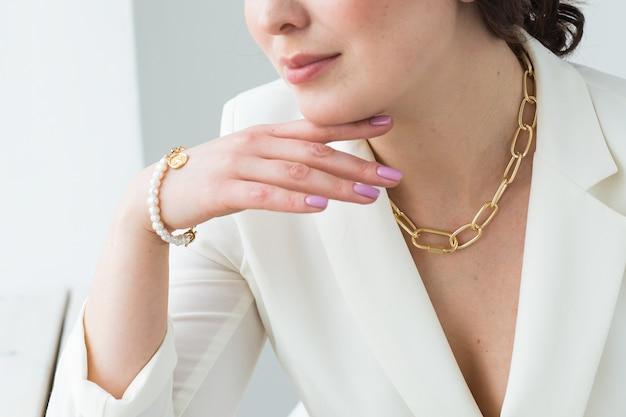 골드 목걸이와 팔찌를 착용하는 여자의 클로즈업. 보석, 보석류 및 액세서리 개념.