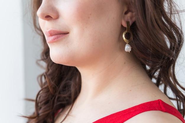 금 목걸이를 착용하는 여자의 클로즈업입니다. 보석, 보석류 및 액세서리.