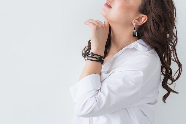 금 목걸이를 착용하는 여자의 클로즈업입니다. 보석, 보석류 및 액세서리. 프리미엄 사진