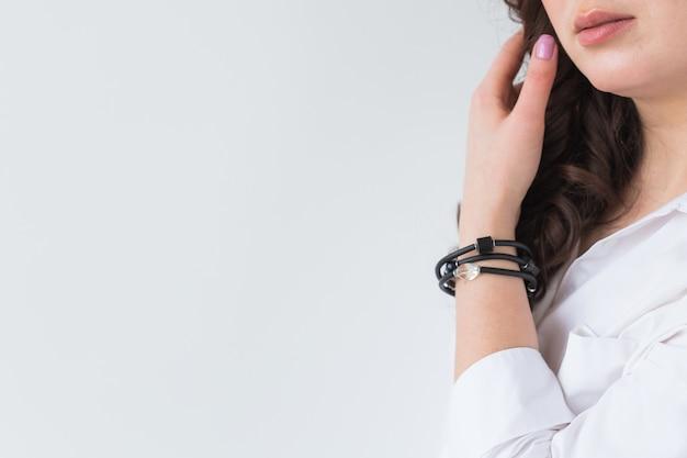 골드 목걸이를 착용하는 여자의 클로즈업입니다. 보석, 보석류 및 액세서리.