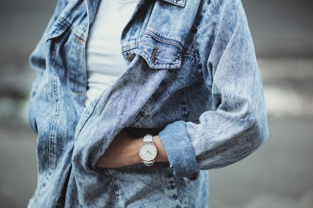 ジーンズのジャケットを着ている女性のクローズアップと時計