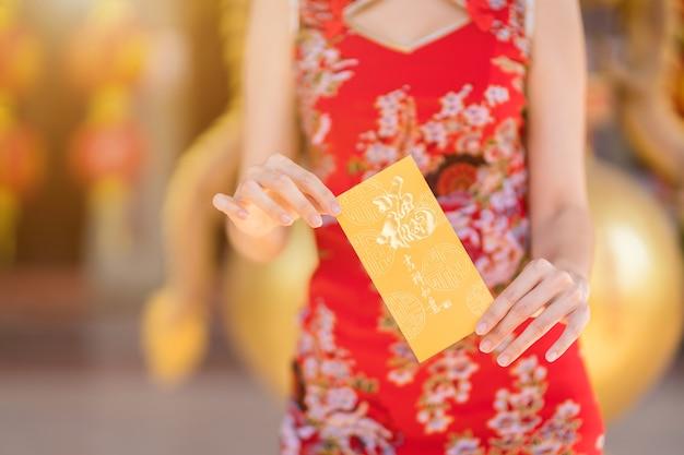 Крупный план женщины в красном традиционном китайском чонсаме, держащей желтые конверты в руке на фестивале китайского нового года в китайском храме