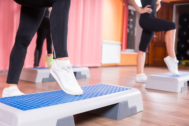 ダンススタジオのバックグラウンドで女性のグループと有酸素運動クラスのステッププラットフォームでつま先タップをしている白いスニーカーを身に着けている女性のクローズアップ