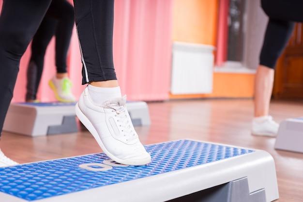 ダンススタジオのバックグラウンドで女性のグループと有酸素運動クラスのステッププラットフォームでつま先タップをしている白いスニーカーを身に着けている女性のクローズアップ Premium写真
