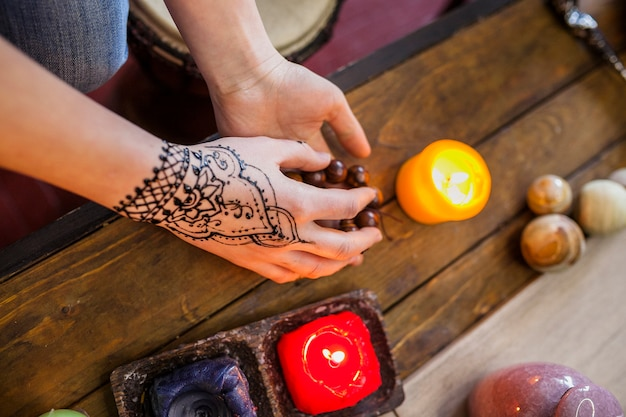 Крупный план женщины с арабским менди на руке, держа бусы на деревянный стол