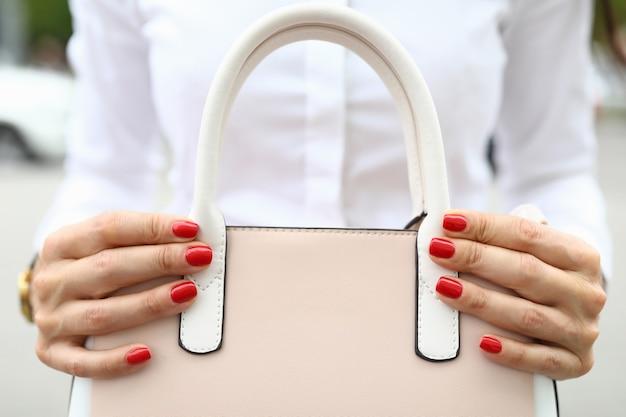 Крупный план женщины с красивым ярко-красным маникюром, держащей модную сумку. пастельно-розовый цвет. стильная сумочка с белыми ручками. роскошная дорогая вещь. концепция моды