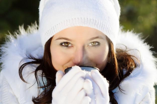 茶色の髪の女性のクローズアップ、毛皮と白い冬の服を着て、金属製のカップから温かい飲み物を飲む