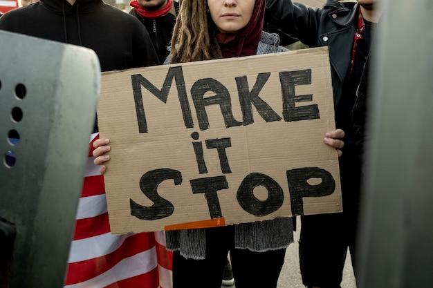 집회 중 군중 속에 서 있는 동안 make stop 마분지 배너를 들고 겁을 먹고 있는 여성의 클로즈업
