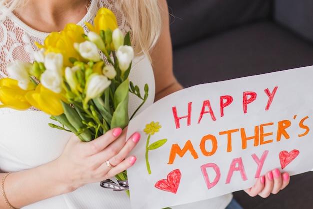 Крупный план женщины с цветами и плакат матери день