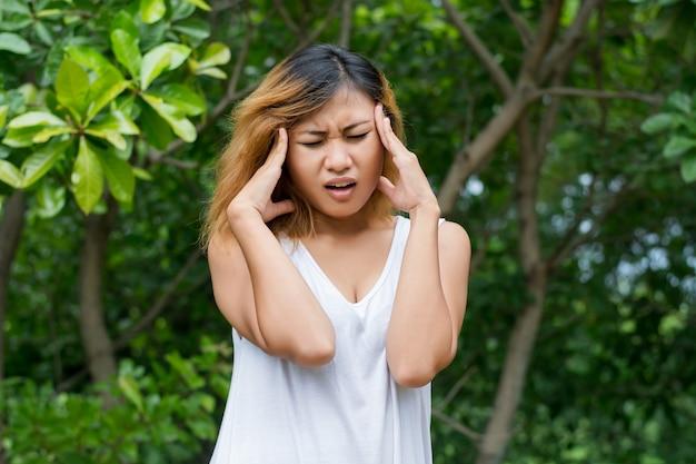 頭痛は彼女の額に触れると女性のクローズアップ