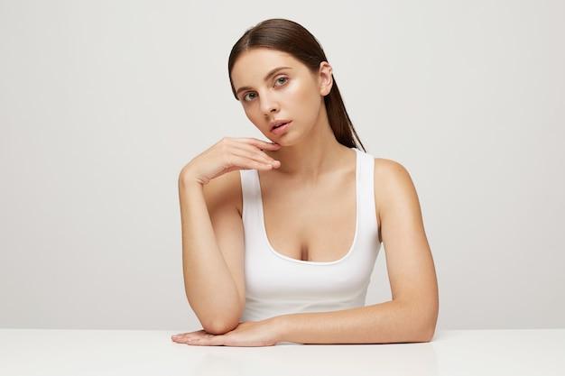 Крупным планом женщина с идеальной здоровой свежей кожей сидит за столом