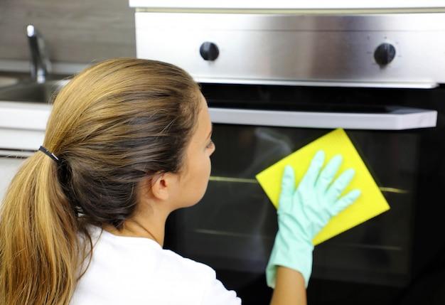 Закройте вверх женщины с защитными перчатками, чистящими дверцу духовки. девушка полирует кухню. люди, работа по дому, концепция очистки.