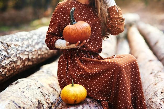 Крупным планом женщины с тыквой в осеннем лесу