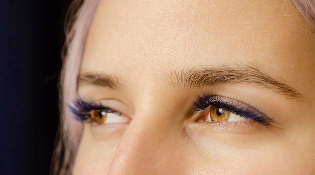 彼女の目に紫の色合いを持つ女性のクローズアップ