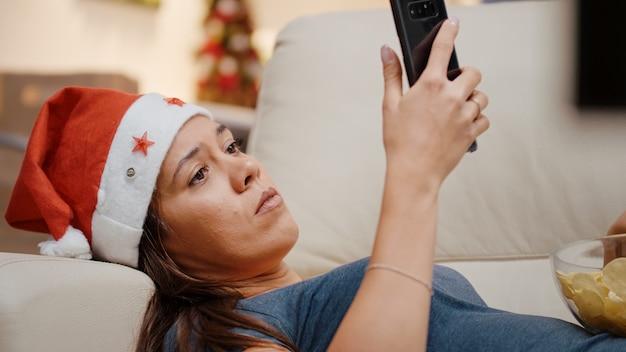 스마트폰 들고 산타 모자와 여자의 클로즈업
