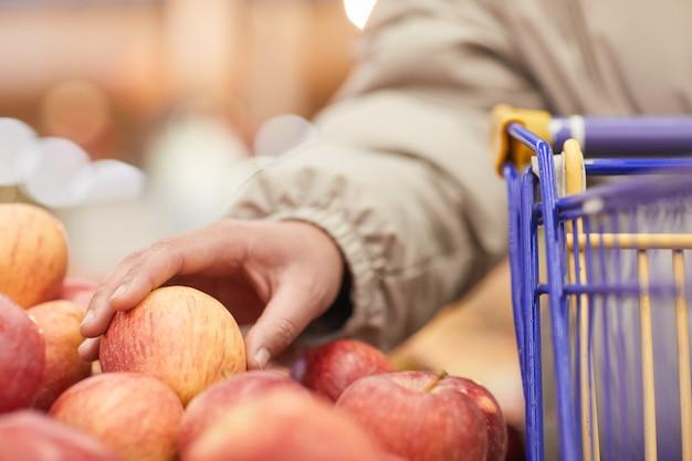 市場で新鮮なリンゴを選ぶショッピングカートを持つ女性のクローズアップ