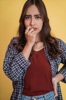 コピースペースで立っている間、心配そうな表情で指を噛む女性のクローズアップ