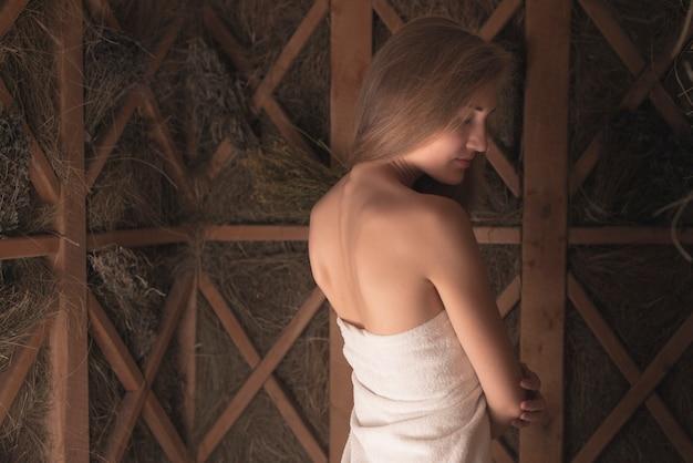 사우나에 서있는 하얀 수건에 싸여 여자의 근접 촬영