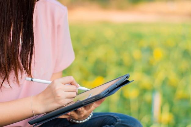 Крупный план женщины, пишущей на планшете ручкой с естественным фоном