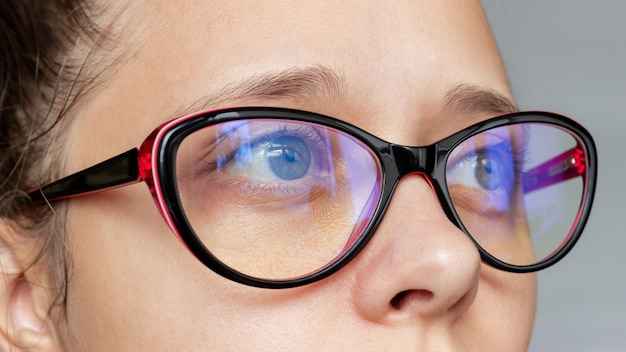 Крупным планом женские глаза в женских очках для работы за компьютером с синими фильтрующими линзами