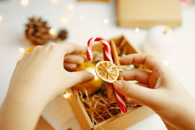 여자 손 클로즈업 크리스마스 선물 상자 흰색 테이블에 사탕 지팡이와 계 피를 넣어 축제...