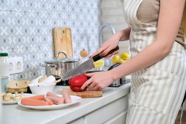 まな板の上で、キッチンで食べ物を調理し、ナイフでパプリカを切る女性の手のクローズアップ