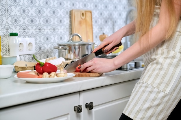 まな板の上で、キッチンで食事を準備し、ナイフでパプリカを切る女性の手のクローズアップ