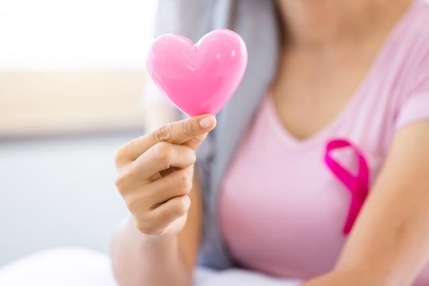 ヘッドスカーフを身に着けているピンクのリボンを持つ女性の癌患者のクローズアップ自宅で形作られた小さなピンクのハートを持って化学療法の治療後、医学の概念