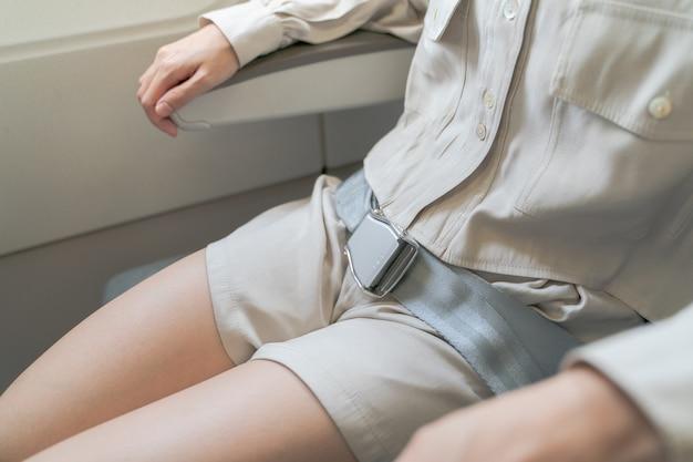 女性のクローズアップは飛行機のシートベルトを締めます。