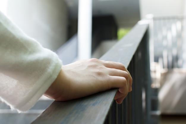 手すりを持っている女性の手のクローズアップ