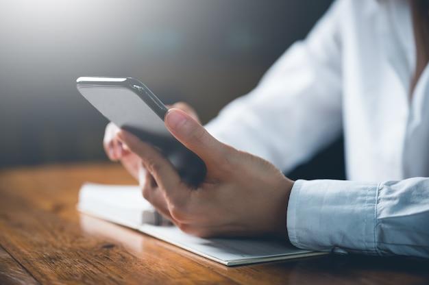 携帯電話または携帯電話を使用して、ウェブサイト、データ、コミュニケーションを備えたソーシャルネットワークを検索するための女性の手のクローズアップ。ビジネスと金融の概念。