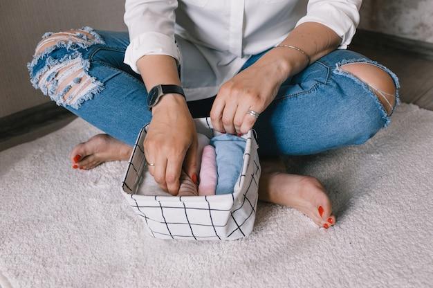 용기와 상자에 물건을 아름답게 접는 여성의 손 클로즈업. 옷장에 액세서리와 속옷을 적절하게 보관한다는 개념