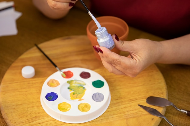 女性の手のクローズアップは、パレットの上に描くために銀色のペンキにブラシを浸します