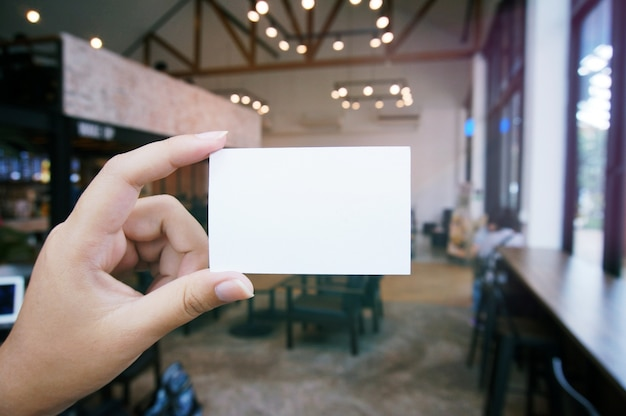 ビジネス名刺を空白のコピースペースの画面を持って女性の手を閉じます。テクノロジーショッピングオンラインコンセプトのスマートフォン