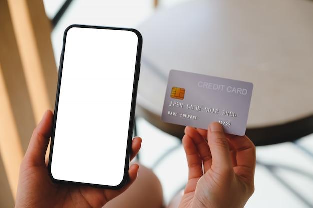 携帯電話と空白のコピースペースとクレジットカードを持っている女性の手のクローズアップ