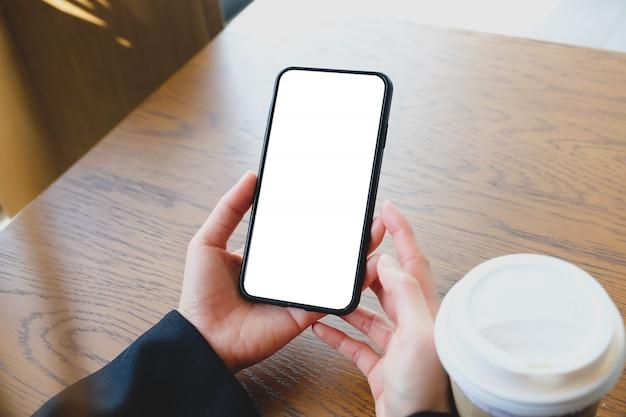 空白のコピースペース画面で携帯電話を保持している女性の手のクローズアップ