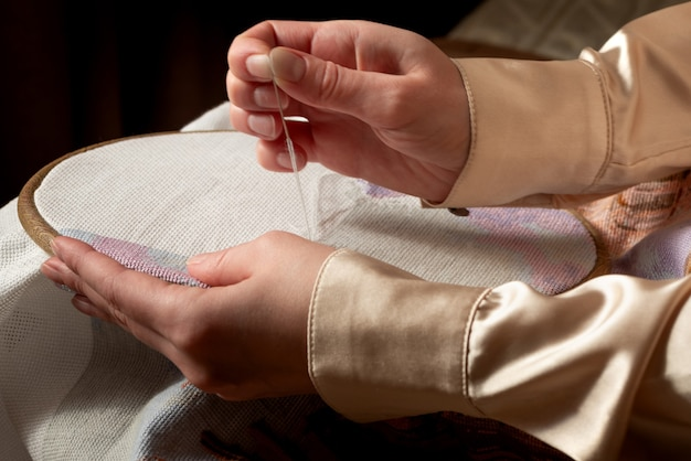 刺繡フレームを保持し、針仕事をしている女性の手のクローズアップ。クロスステッチ、趣味、diy